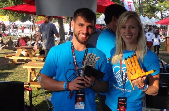 Maker Faire New York 2014: e-Nable Booth featuring a young adult male at left and a young adult female at right, both of whom are holding prosthetic arms in their hands.