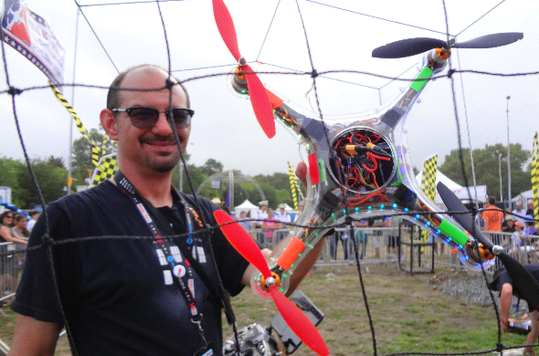 Maker Faire New York 2014: War of Drones photo showing an adult male gentleman holding a large drone in one hand. He is standing in the Game of Drones cage arena.