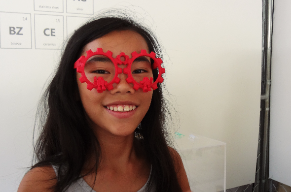 Maker Faire New York 2014: tween girl wearing 3D printed red polyamide glasses at our booth