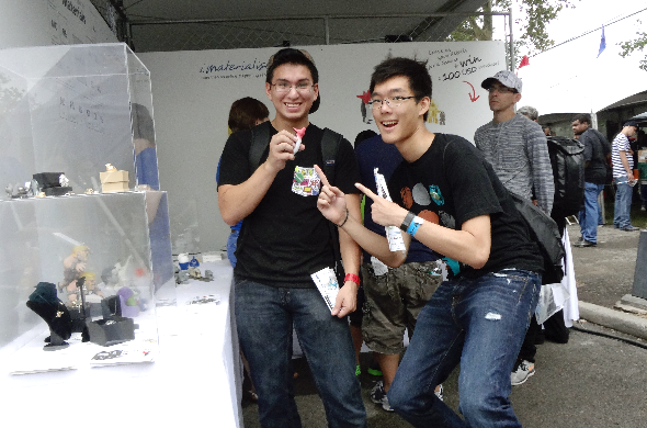 New York Maker Faire 2014: image of two young men smiling brightly in our booth, striking a finger-pointing pose