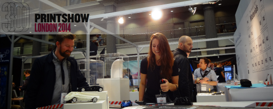 Header Picture from the 2014 London 3D Printshow featuring a gentleman and a lady in her early 20s playing with the 3D printed race cards on our slot car track