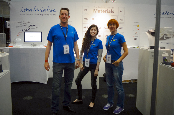 Picture from the 2014 London 3D Printshow featuring Rebecca Roxy Maas, Darya Kireyeva, and Sam Vandormael standing together in front of the i.materialise booth.