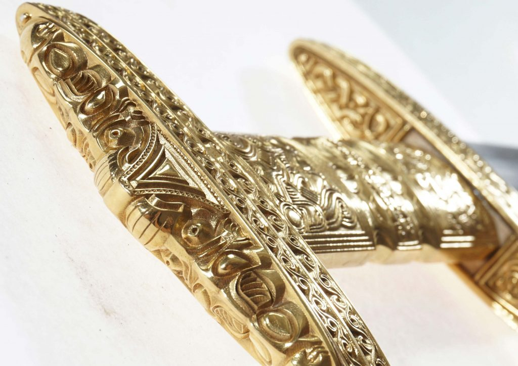 The ornate bronze handle of a sword.