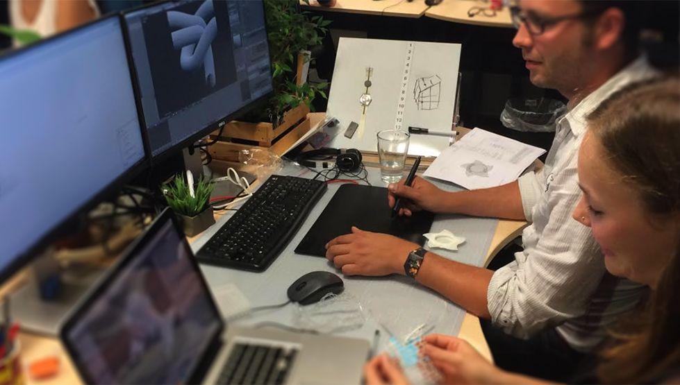 גבר ואישה יושבים ומעצבים דגם תלת מימד דיגיטלי, המוצג על מסך מחשב.